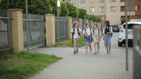 Skolbarn med ryggsäckar i solnedgångljus som hem kommer från skola tillbaka ungeskola till stock video