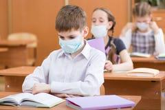 Skolbarn med skyddsmaskeringar mot influensavirus på kursen i klassrum Royaltyfria Bilder