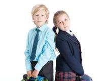 Skolbarn med stående påsar tillbaka som ska dras tillbaka, isolerad vit bakgrund Royaltyfri Foto