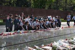 Skolbarn satte blommor till den eviga branden på minnesmärken Royaltyfri Fotografi