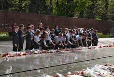 Skolbarn satte blommor till den eviga branden på minnesmärken Fotografering för Bildbyråer