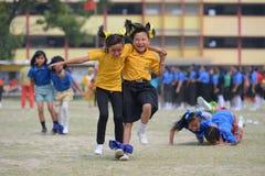 Skolbarn som deltar i ett tre lagt benen på ryggen häcklopp Royaltyfria Bilder