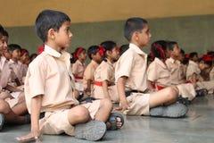 Skolbarn som gör yoga med lärarna arkivfoton