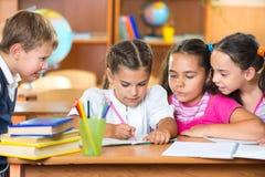Skolbarn som har gyckel i klassrum royaltyfria bilder