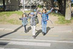 Skolbarn som korsar gatan Arkivfoton