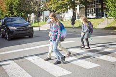Skolbarn som korsar gatan Royaltyfri Bild