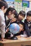 Skolbarn som ser ett jordklot i klassrumet Arkivfoto