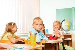 Skolbarn som sitter på tabeller under geografi arkivfoto