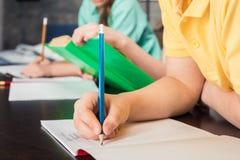 Skolbarn som skriver med blyertspennor Arkivfoton