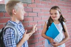 Skolbarn som till varandra talar i korridor Arkivbilder