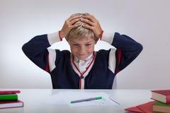 Skolbarn som trycker på hans huvud royaltyfri bild