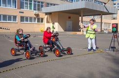 Skolbarn spelar på platsen enligt reglerna av vägen Arkivfoto