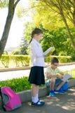 Skolbarn utomhus, i parkerar, att läsa böcker och göra läxa royaltyfria bilder