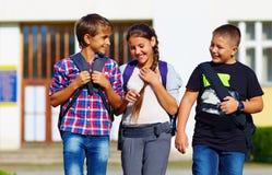 Skolbarn vänner som går från skolan, med- sympati Arkivfoto
