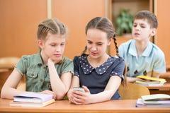 Skolbarnflickan visar mobiltelefonen till vänner arkivfoto