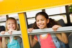 Skolbuss: Flickor som ut ser bussfönstret Arkivbild