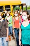 Skolbuss: Grupp av studenter som bär framsidamaskeringar Royaltyfri Foto