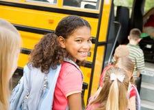 Skolbuss: Gullig flicka som får på bussen arkivbilder