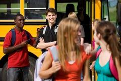 Skolbuss: Guy Flirts med skolflickan Arkivbild