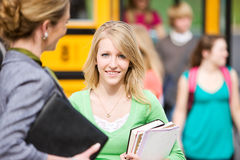 Skolbuss: Nätt tonårigt anseende med läraren Royaltyfri Bild