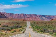 Skolbuss på en ökenhuvudväg i sydliga Utah Royaltyfri Fotografi