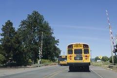 Skolbuss på järnvägkorsningen Arkivbild
