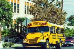 Skolbuss som parkeras av skolan royaltyfri fotografi