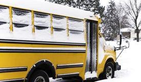 Skolbuss som parkeras i en bostads- grannskap under en snö da arkivbild
