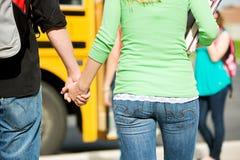 Skolbuss: Tonåriga studenthållhänder Royaltyfria Foton