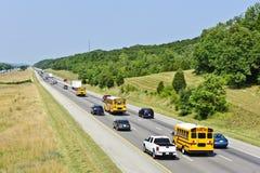 Skolbussar med annan trafik royaltyfria bilder