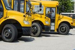 Skolbussar uppställda för att transportera ungar Arkivfoto