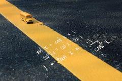 Skolbussleksakmodell och matematikformular Fotografering för Bildbyråer