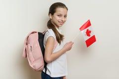 Skolflicka 10 år i den vita T-tröja med en ryggsäck som rymmer flaggan av Kanada Royaltyfri Fotografi