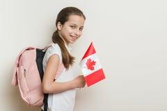 Skolflicka 10 år i den vita T-tröja med en ryggsäck som rymmer flaggan av Kanada Arkivfoton