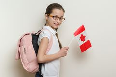 Skolflicka 10 år i den vita T-tröja med en ryggsäck som rymmer flaggan av Kanada, ljus vägg för bakgrund i skolan Royaltyfri Foto