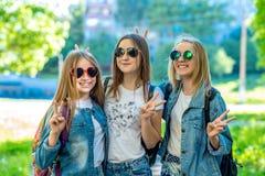 Skolflicka för flicka för tre flickavänner Sommar i natur I jeanskläder bak ryggsäckar I solglasögon Gest av händer arkivfoto