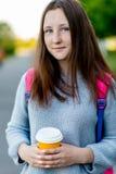 Skolflicka för tonårs- flicka I sommar i parkera I hans händer rymmer ett exponeringsglas av kaffe eller te bak hans ryggsäck royaltyfri bild