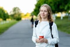 Skolflicka för tonårs- flicka I sommaren parkera in I hans händer rymmer ett exponeringsglas av kaffe eller te bak hans ryggsäck  royaltyfria foton