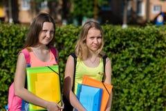 Skolflicka för två flickor Sommar i natur Han rymmer anteckningsböcker och läroböcker i hans händer Begrepp snart till skolan arkivbilder