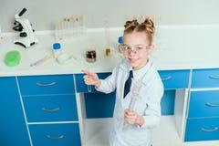 Skolflicka i skyddsglasögon som rymmer agens i flaskor i kemisk labb Royaltyfria Foton