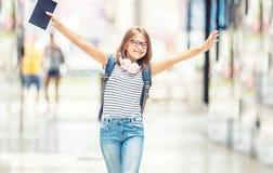 Skolflicka med påsen, ryggsäck Stående av den moderna lyckliga tonåriga skolaflickan med den påseryggsäckhörlurar och minnestavla royaltyfri bild