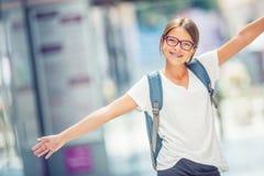 Skolflicka med påsen, ryggsäck Stående av den moderna lyckliga tonåriga skolaflickan med påseryggsäcken Flicka med tand- hänglsen fotografering för bildbyråer