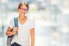 Skolflicka med påsen, ryggsäck Stående av den moderna lyckliga tonåriga skolaflickan med påseryggsäcken Flicka med tand- hänglsen royaltyfri bild