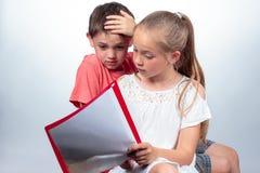 Skolflicka och skolflicka som tillsammans studerar Arkivbild
