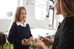 Skolflicka på en grundskola för barn mellan 5 och 11 år som framlägger upp en gåva till hennes lärarinna i ett klassrum, midja, s arkivfoto