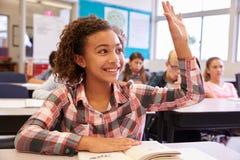 Skolflicka på skrivbordet i grundskolan som lyfter hennes hand arkivfoton
