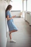 Skolflicka som använder mobiltelefonen i korridor arkivbilder