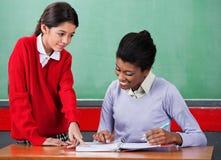 Skolflicka som frågar fråga till lärarinnan At Arkivfoto