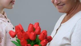 Skolflicka som ger blommor till l?raren, lyck?nskan p? 8 mars, tacksamhet arkivfilmer