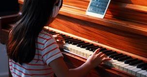 Skolflicka som lär pianot i musikgrupp 4k